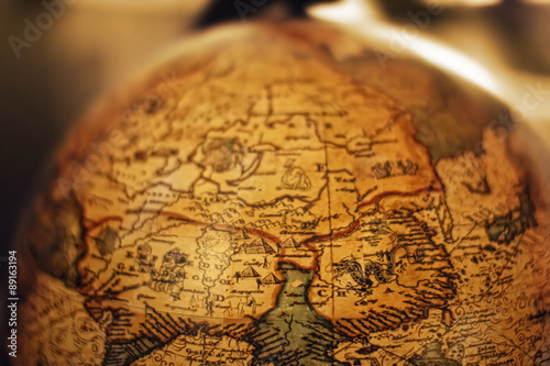 Fotobehang Wereldkaart Close up of old vintage globe with old handmade map soft colors