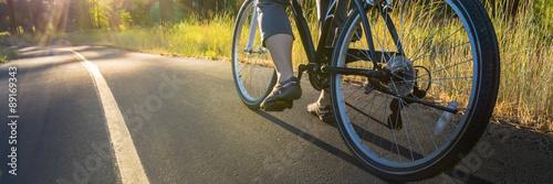 Foto op Plexiglas Fietsen Bike on the asphalt path illuminated by sun.