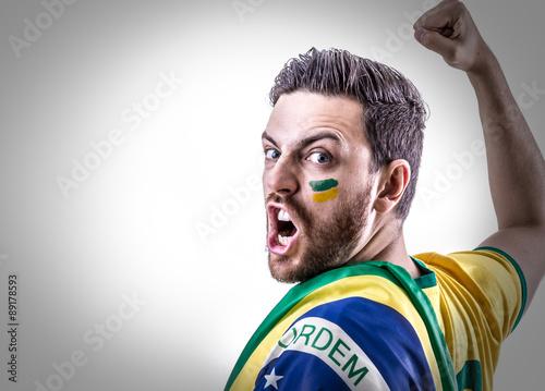 Fotografie, Tablou  Man holding the Brazilian flag on white background