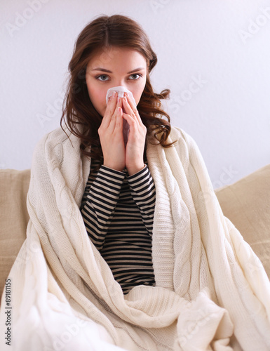 Fotografia  Portrait of a sick woman blowing her nose while sitting on the