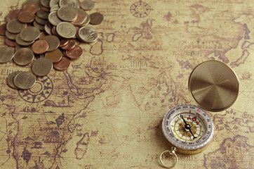 Vintage compass and coins on old map