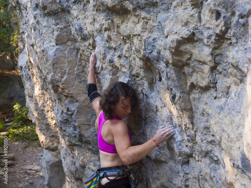 Foto op Plexiglas Alpinisme Young woman with rope climbs on the rock.