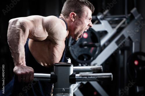 fototapeta na szkło Mann trainiert Dips im Fitnessstudio