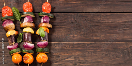 Fotografía  Grilled veggie skewers at left side old rustic wooden background
