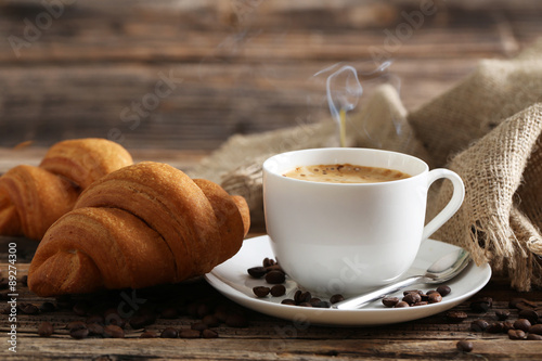 Fototapety, obrazy: Delicious croissants with cup of coffee on brown wooden backgrou