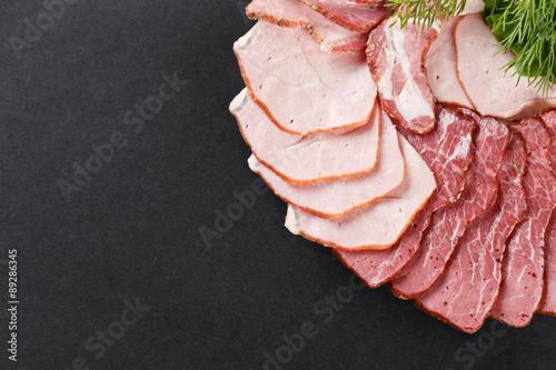 Fotografie, Obraz  cutting ham with vegetables assortment on black background