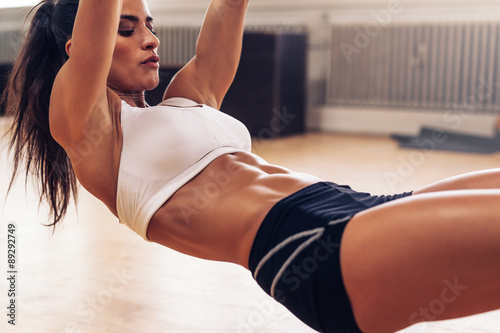 Fit young woman exercising at gym Plakat