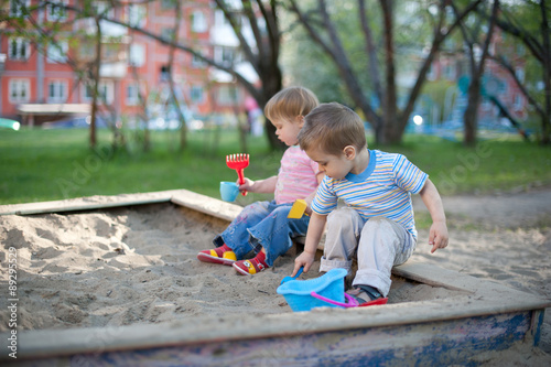 Fotografie, Obraz  Two cute little children brother and sister playing in a sandbox