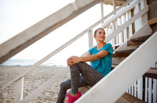 Woman In Fitness Gear Relaxing On Beach House Steps