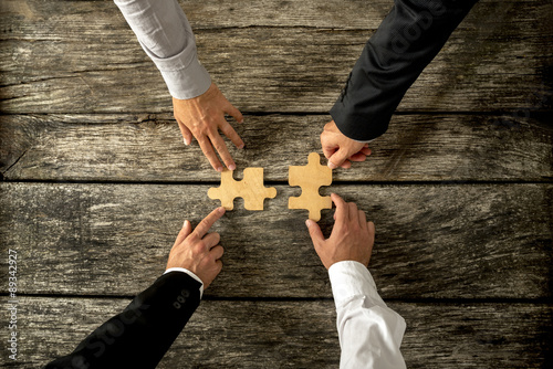 Fotografie, Obraz  Four successful business men joining two puzzle pieces each bein