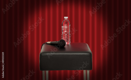 Fotografie, Tablou  Bottle of water next to a microphone on a stool in the stage