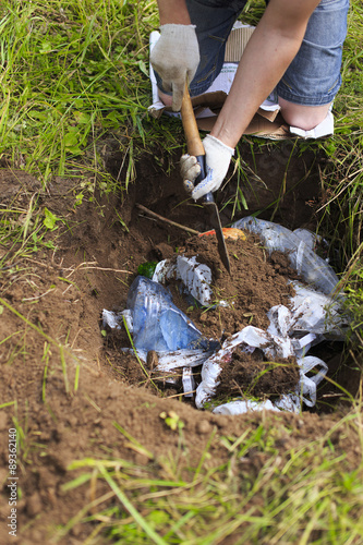 Fotografia, Obraz  bury trash. man in camping removes household rubbish into a hole