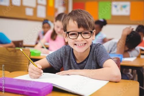 Fényképezés Little boy working at his desk in class
