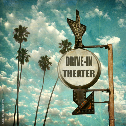 Photo  aged and worn vintage photo of retro drive in theater sign