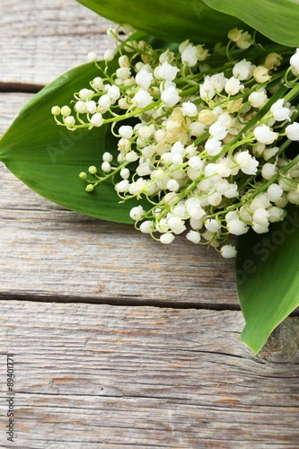 Wall Murals Lily of the Valley with leaves on grey wooden background