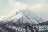Wysoki skalisty szczyt w słoneczny dzień w zimie - 89406551