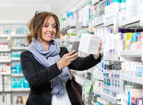Fotografie, Obraz  Smiling Customer Scanning Product Through Mobile Phone In Pharma