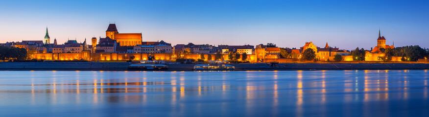 Panorama of Torun at night reflected in Vistula river, Poland