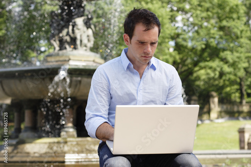 Photo  Man sitting a fountain working on laptop computer.