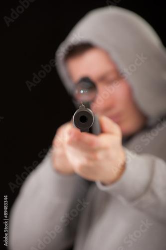 Fotografía  Sniper in hood aims at rifle