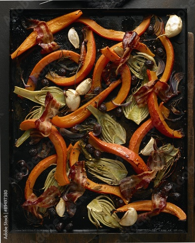 Valokuva  A pumpkin-fennel medley with garlic and bacon on a baking tray