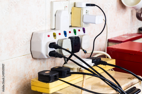 Fotografiet Multiple electricity plugs on adapter risk overloading and dangerous