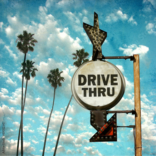 Fotografie, Obraz  aged and worn vintage photo of drive thru sign with palm trees