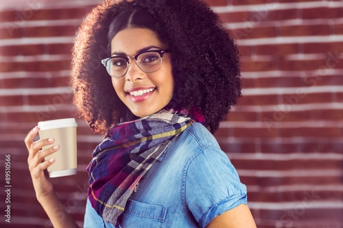 Smiling attractive hipster holding take-away cup