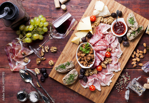 Keuken foto achterwand Oost Europa Prosciutto, cheese, grapes, red wine on a wooden table, bird's-eye view