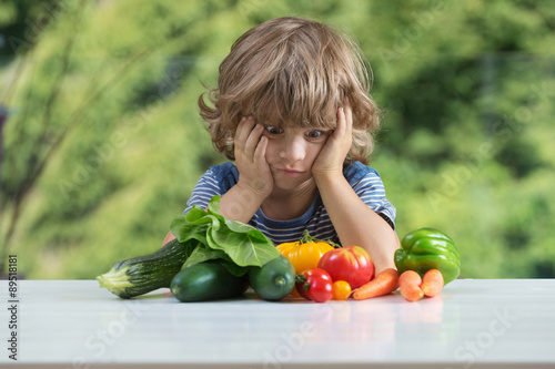 Fotografia  Cute little boy sitting at the table, unhappy with his vegetable meal, bad eatin