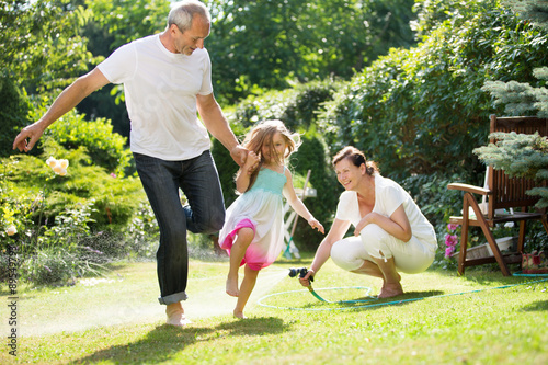 Girl and grandparents playing and waterin garden Poster