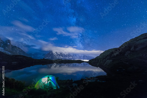 France, Mont Blanc, Lake Cheserys, lit tent on the shore of the lake by night with Milky way and Mount Blanc reflected in the lake