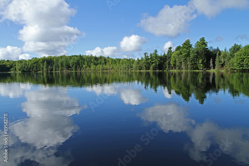Foto op Aluminium Meer / Vijver Puffy Clouds Reflected in Calm Lake