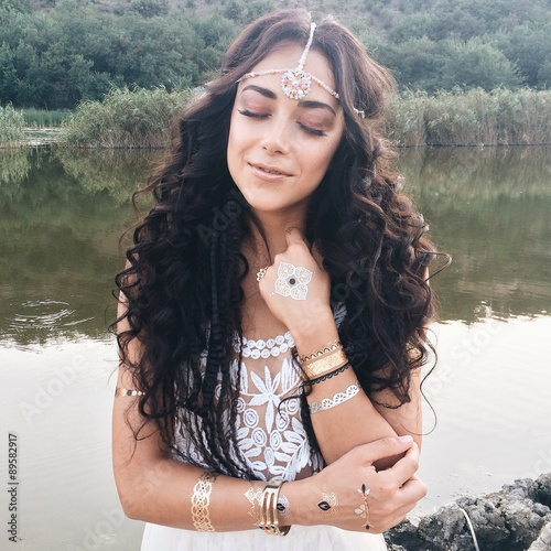 young beautiful woman in a boho style dress posing near lake