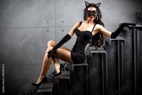 Cuadros en Lienzo sexy woman in catwoman suit lying on stairs