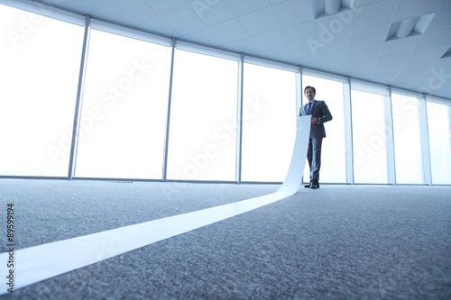 Fényképezés  Office worker unrolling long sheet