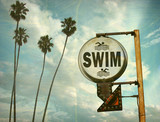 Fototapeta Młodzieżowe - aged and worn vintage photo of swim sign at beach