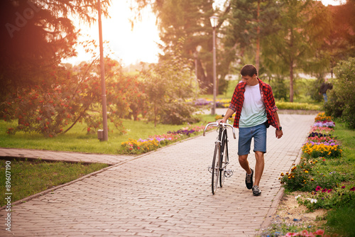 Hipster man with bicycle walking in the park Wallpaper Mural