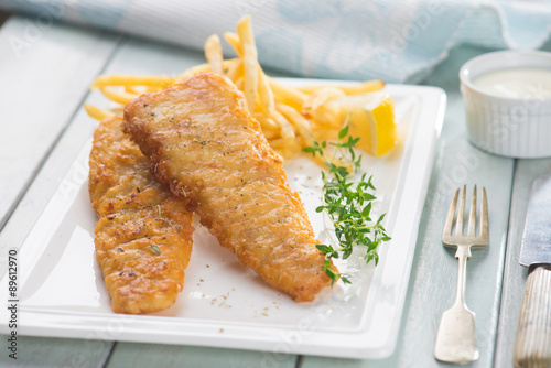 Deurstickers Klaar gerecht Fish and chips. Fried fish fillet with french fries wrapped by p