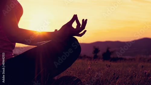 Poster School de yoga Young athletic woman practicing yoga on a meadow at sunset, silhouette
