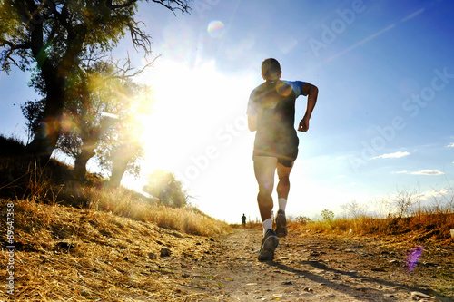 Fotografie, Obraz  Silueta mladého sportovního muže běží off road běžecké soutěže na západ slunce