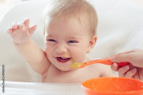 fototapeta na lodówkę Bebé hermoso comiendo puré