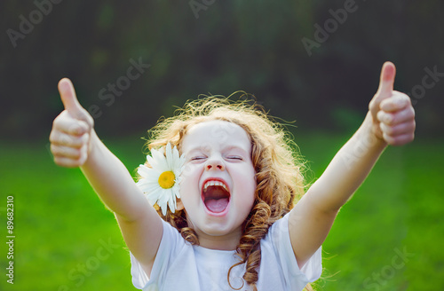 Fotografia  Laughing girl showing thumbs up.