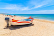 Typical colourful fishing boat on sandy beach in Armacao de Pera village, Algarve region, Portugal