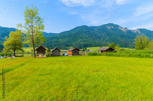 Poster Lime groen Green meadow in small alpine village on shore of Weissensee lake with traditional boat houses in background, Austria