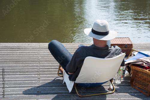 Fotografia, Obraz  Man relaxt aan de waterkant op een steiger met smartphone