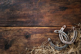 Fototapeta Konie - Two old rusty horseshoes with straw on vintage wooden board