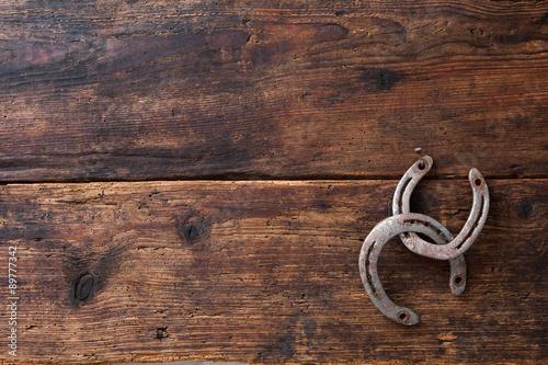 Foto op Canvas Paarden Two old rusty horseshoe on vintage wooden board