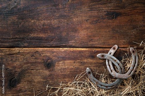 Poster Paarden Two old rusty horseshoes with straw on vintage wooden board