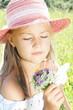 Mädchen mit Hut und Blumenstrauss auf einer Wiese